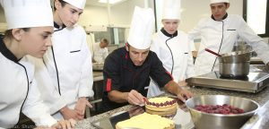 Four student chefs watching a teacher decorate a cake 300x144 - Four-student-chefs-watching-a-teacher-decorate-a-cake